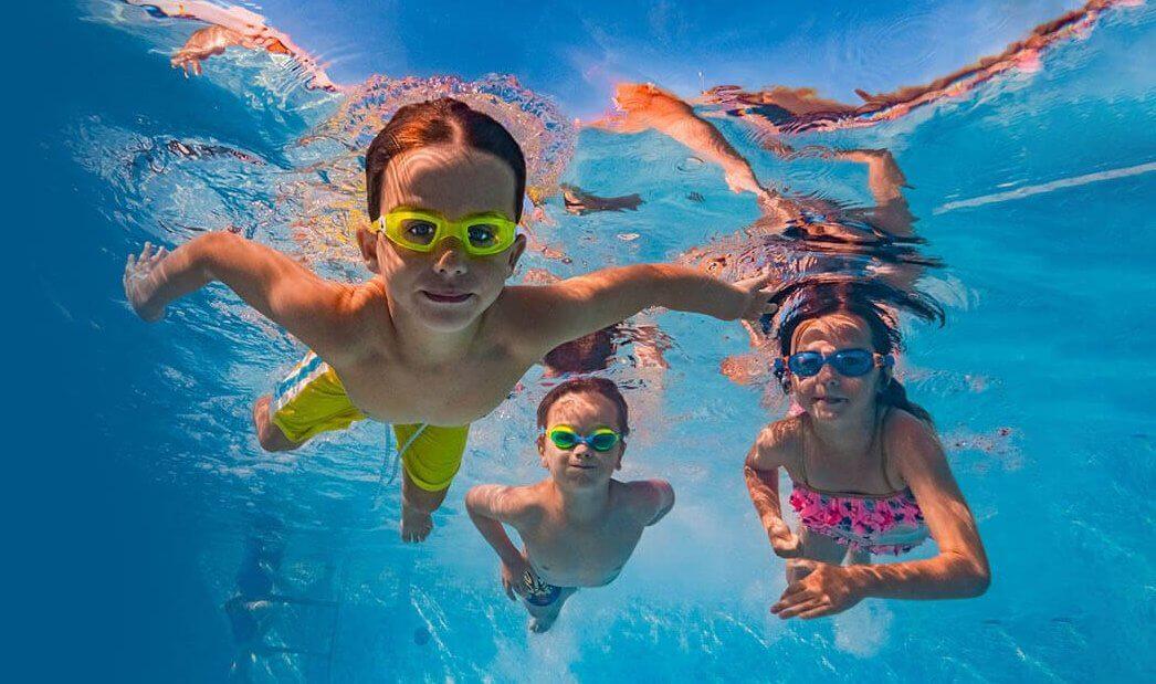 3 kids swimming underwater in pool